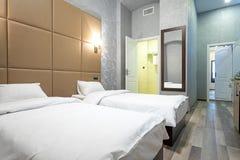 Rum med en dubbelsäng, nattduksbord, spegel på väggen, vit dörr som är ljusa - gråa väggar, laminatdurk och en passage till bathr royaltyfri bild