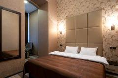 Rum med en dubbelsäng, nattduksbordet, spegeln på väggen, den vita dörren, beigea väggar, laminatdurken och en passage till badru royaltyfria bilder