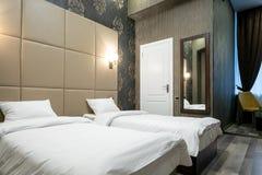 Rum med en dubbelsäng, nattduksbordet, spegeln på väggen, den vita dörren, fönstret med gardiner, laminatdurken och en passage ti royaltyfria bilder
