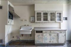 Rum med vasken i ett övergett sjukhus Arkivfoto
