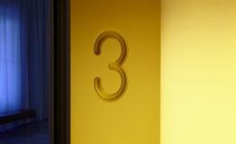 Numrera 3 på dörr Arkivfoto