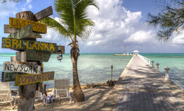 Rum Point Dock and Signpost. A signpost with various destinations next to the blue-green crystal clear waters off Rum Point dock on the north side of Grand stock photos