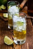 Rum on the rocks (for a Cuba Libre longdrink). On wooden background royalty free stock image