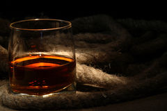 Rum And Rope. Closeup of glass of rum near rope on dark background stock photo