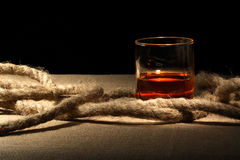 Rum And Rope. Closeup of glass of rum near rope on canvas surface Stock Photo