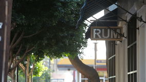 Rum Sign Hangs Under a Blue Awning and Green Trees on a Windy Day. Shot of a sign that says, RUM on it. It is under a blue awning and near green trees on a windy stock video footage