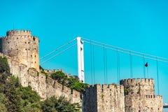 Rumeli Hisari fästning på Bosporusen, med den västra delen av Fatih Sultan Mehmet Bridge som förbinder Europa och Asien arkivbild