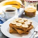 Rumiana grzanka z masłem orzechowym, pokrojeni †‹â€ ‹banany, kawa, br Obrazy Stock