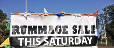 Rummage Sale Sign. A rummage sale sign advertises to people traveling by in their cars that there is a yard sale today Stock Photo