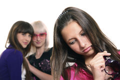 Rumour. Three young girls: two are gossiping against the third royalty free stock photo