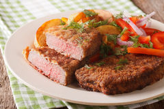 Rump steak in breadcrumbs and fresh vegetables, baked potatoes c. Fried rump steak in breadcrumbs and fresh vegetables, baked potatoes close up on the table Stock Images