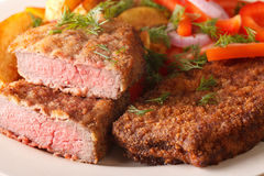 Rump steak in breadcrumbs and garnished with vegetables macro ho Royalty Free Stock Photography