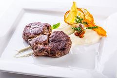 Rump steak. Close up Tender Grilled Beef Meat on White Plate with vegetable decoration. Stock Image