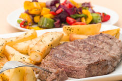 Rump steak and fries. Rump steak and chunky herby fries dinner with a side dish of roasted mixed vegetables - studio shot Stock Images