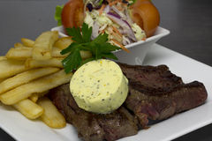 Rump steak with herb butter meal. Steak meal with garlic butter, fries and coleslaw Stock Images