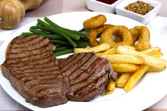 Rump steak. With onion rings chips and green beans Royalty Free Stock Image