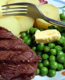 Rump steak peas potato macro. Grilled rump steak, peas with a knob of butter, boiled potatoes and a fork Royalty Free Stock Photography