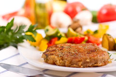 Rump steak with potatoes and vegetables. Rump steak with roasted potatoes, fried vegetables and mushrooms on a white plate with raw ingredients in the back Royalty Free Stock Image