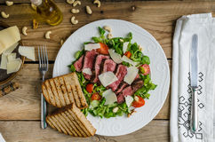 Rump steak with spicy herb butter. Nuts and little salad, sprinkled with parmesan and little panini bread Royalty Free Stock Photo
