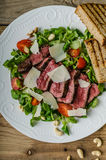 Rump steak with spicy herb butter. Nuts and little salad, sprinkled with parmesan and little panini bread Royalty Free Stock Photography