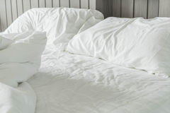 Rumpled bed with white messy pillow decoration in bedroom Stock Photo