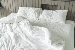 Rumpled bed with white messy pillow decoration in bedroom Royalty Free Stock Images