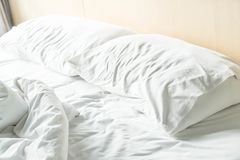 Rumpled bed with white messy pillow Royalty Free Stock Photos