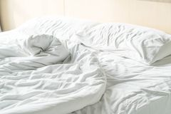Rumpled bed with white messy pillow Royalty Free Stock Image