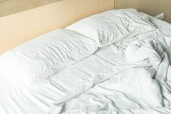 Rumpled bed with white messy pillow Stock Photography