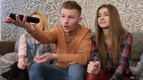 Rumskamrater som väljer film för att hålla ögonen på på tv Arkivbilder