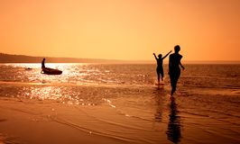 Run. Silhouette image of two girls playing on the beach Royalty Free Stock Image