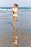 Run. Slim girl running along the beach royalty free stock photo