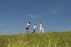 Run 3. Three young nice girls running on a green grass on a background of the blue sky Royalty Free Stock Photo