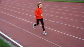 Run. Woman in the orange tracksuit running on the running track Royalty Free Stock Photography