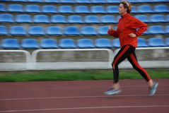 Run. Woman in the orange tracksuit running on the running track Stock Photo