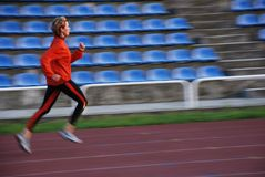 Run. Woman in the orange tracksuit running on the running track Royalty Free Stock Images