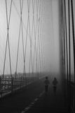 Run. A pair of joggers run along the Brooklyn Bridge on a foggy morning Royalty Free Stock Images