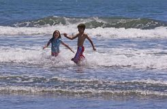Run Away. Two children running from the waves Royalty Free Stock Image