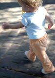 Run Baby Run. Narrow focused action shot of a running child with a pacifier stock photos