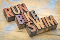 Run, bike, swim in wood type Stock Photo