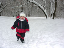 Run boy in winter wood Royalty Free Stock Images