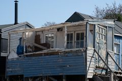 Run down blue large wooden shack by the coast stock photography