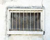 Run down exterior basement window in need of repair.  Outer metal bars installed to prevent intrusions. Royalty Free Stock Image
