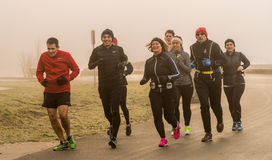 Run in the foggy. The guys are running in a chilly foggy winter morning at Sunset beach stock images