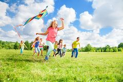 Run with kite for fun. Happy little girl running with kite and her friends on the summer green field on sunny day Royalty Free Stock Photography
