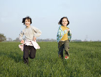Run of little girls. On the spring field Royalty Free Stock Photography