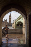 On the run in London. LONDON, UK - MARCH 6, 2016: Jogger runs through arch with Big Ben and Westminster bridge in background Stock Photography