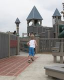 Run & Play. Young boy running into playground Royalty Free Stock Image