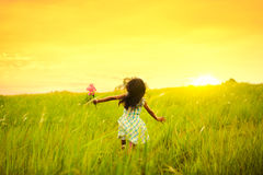 Run and Play. Little girl running on meadow with sunset Royalty Free Stock Photo