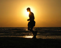 Run to the sun. Man running on the beach at sunset Stock Images